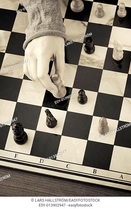 Hand moving chess piece. Conceptual image of decision, choice and strategy