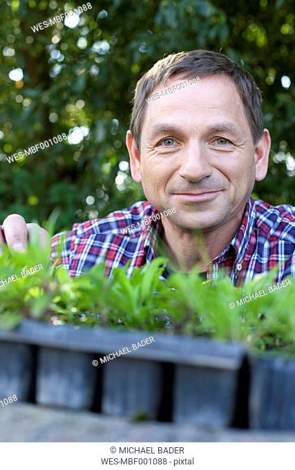 Germany, Saxony, Mature man with potted plant, smiling, portrait