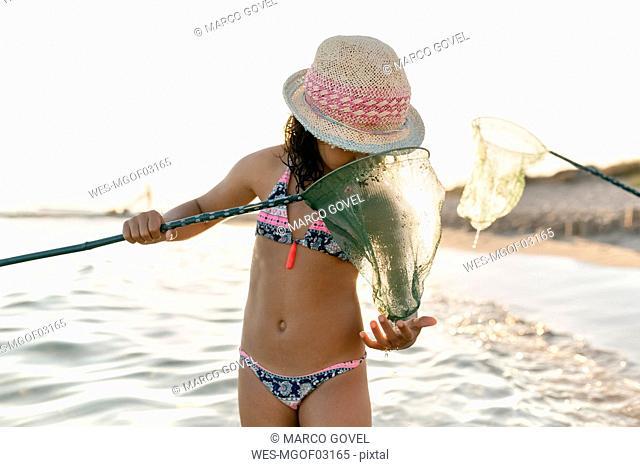 Spain, Menorca, girl with a dip net on the beach
