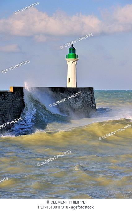 Wave crashing into mole with lighthouse during rough sea at Saint-Valéry-en-Caux, Normandy, France