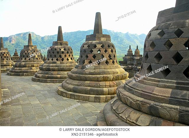 View of the Menoreh Hills and Kedu Plain through some of the 72 stupas atop the 9th-Century Mahyana Buddhist Temple at Borobudur, Central Java, Indonesia