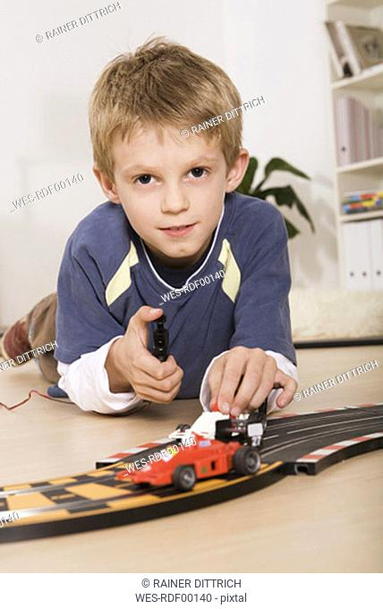 Child (7-9) playing with toy cars