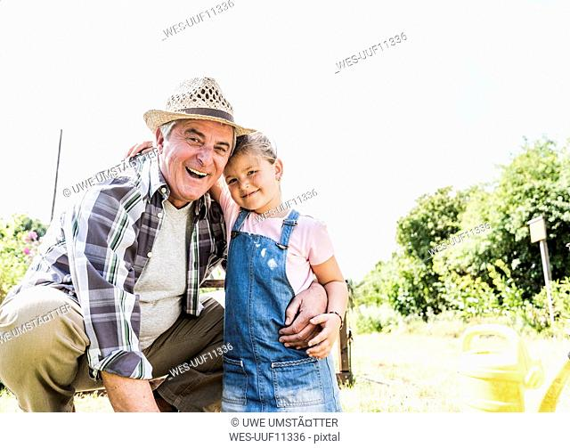 Portrait of happy grandfather and granddaughter in the garden