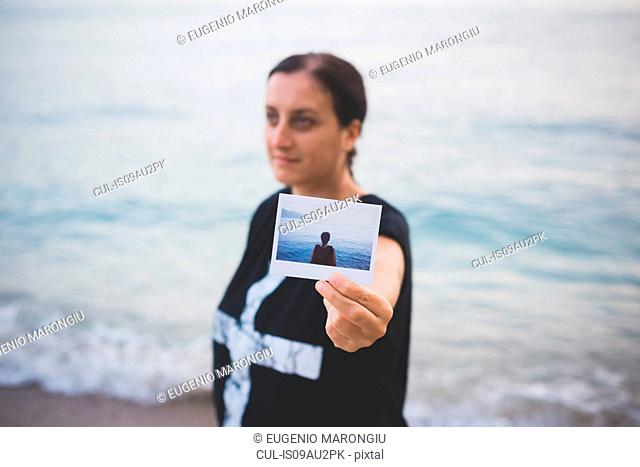 Woman holding up photograph of herself on beach