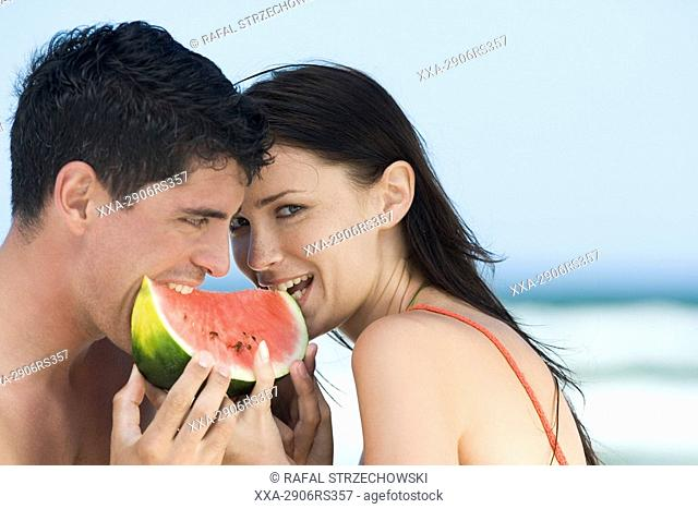 couple eating watermelon on beach