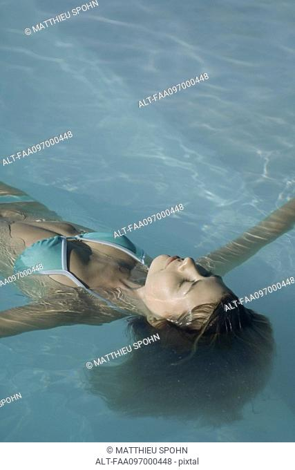 Young woman floating in swimming pool, eyes closed