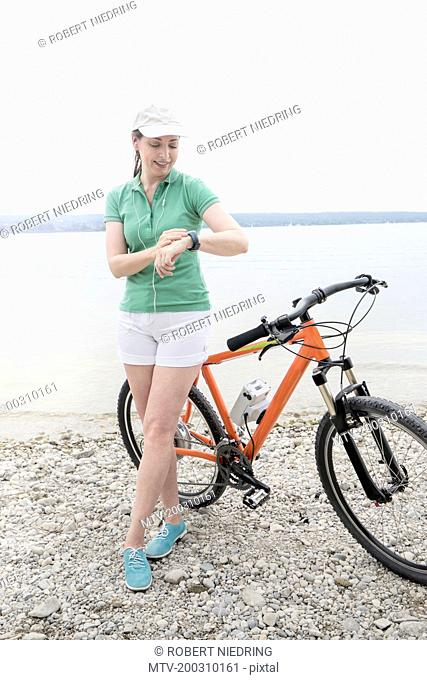 Mature woman with electric bike by lake checking the time, Bavaria, Germany