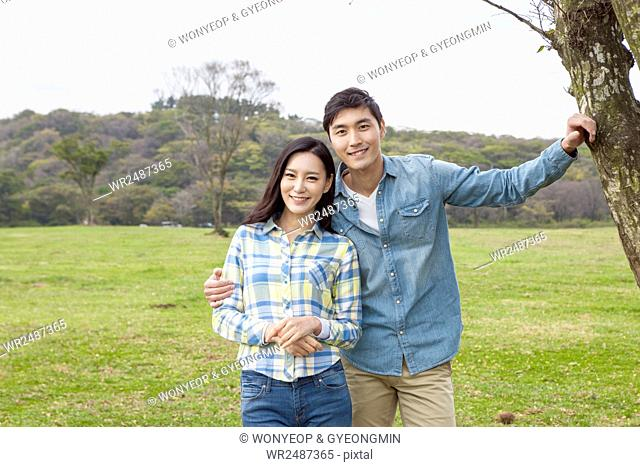 Young smiling couple having a date on grassland