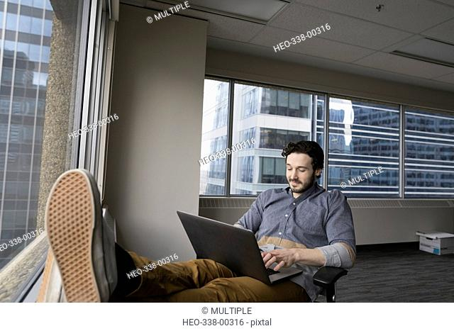 Businessman working at laptop with feet up in urban new office