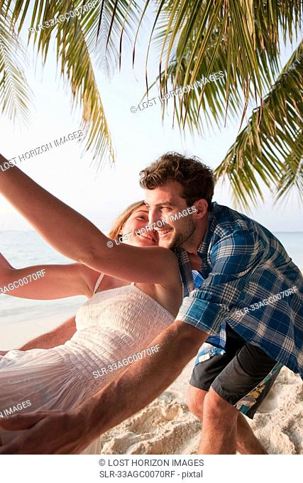 Couple playing on swing at beach
