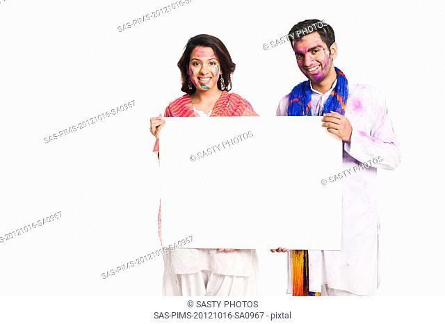 Couple celebrating Holi and holding a blank placard