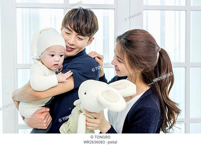 Portrait of loving parents holding their baby and doll
