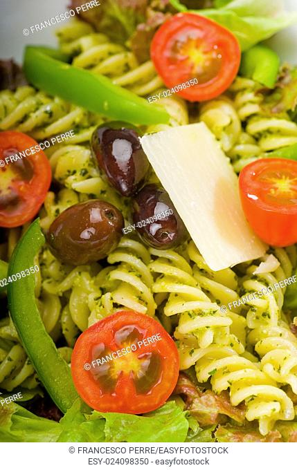fresh healthy homemade italian fusilli pasta salad with parmesan cheese,pachino cherry tomatoes, black olives and mix vegetables