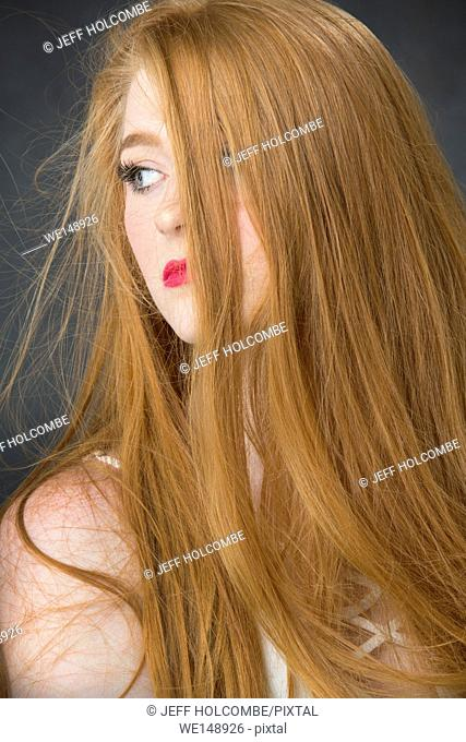 Head and shoulders portrait of beautiful young woman with bountiful red hair, head turned aside