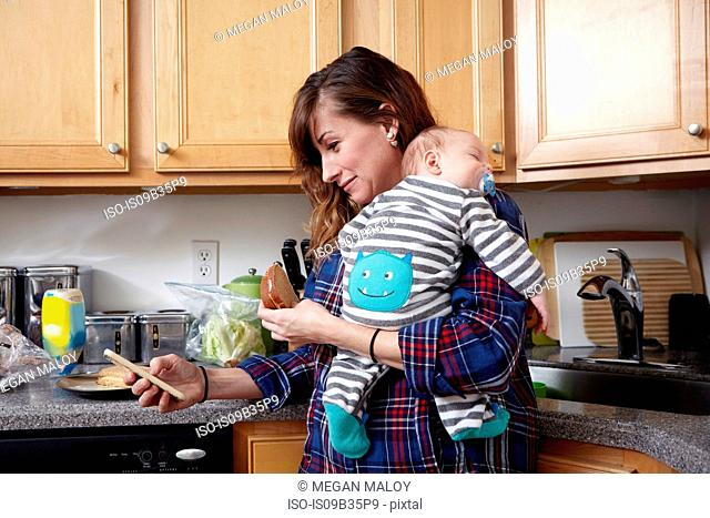 Mother holding sleeping baby boy and looking at smartphone