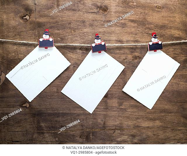 three paper vintage postcards hanging on a rope, brown wooden background