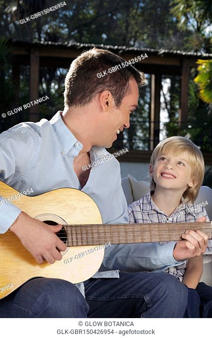 Man playing a guitar with his son sitting beside him