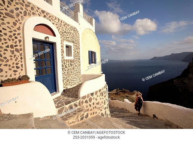 Woman walking down the steps in Oia town, Santorini, Cyclades Islands, Greek Islands, Greece, Europe.1015