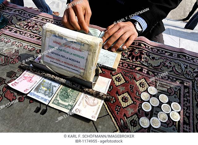 Table of a donation collector, Turkish banknotes and coins lying on a carpet, Blue Mosque, Sultan Ahmet Camii, Sultanahmet, Istanbul, Turkey