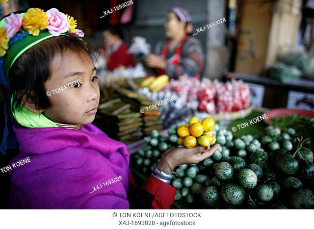 Longneck girl holding fruit at a market stand Approximately 300 Burmese refugees in Thailand are members of the indigenous group known as the Longnecks The...