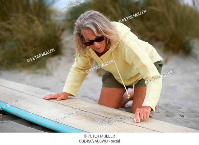 Senior woman on beach, waxing surfboard