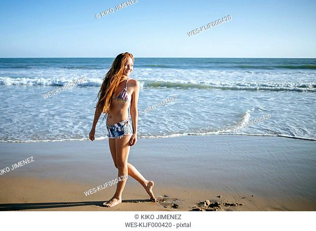 Smiling young woman walking on the beach