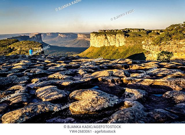 Person looking at the Vale do Capao from the Morro do Pai Inacio and heart shaped stone in foreground, Chapada Diamantina, Bahia, Brazil
