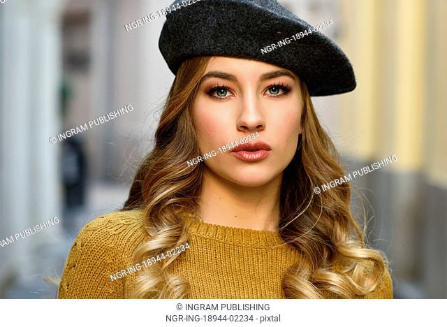 Blonde russian woman in urban background. Beautiful young girl wearing beret, black leather jacket and mini skirt standing in the street