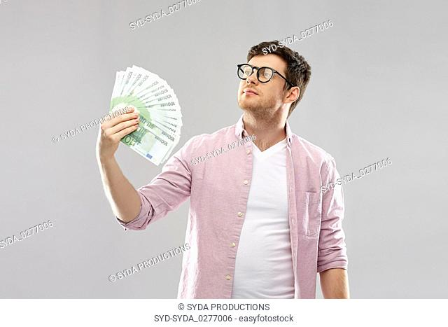 proud young man in glasses with fan of euro money