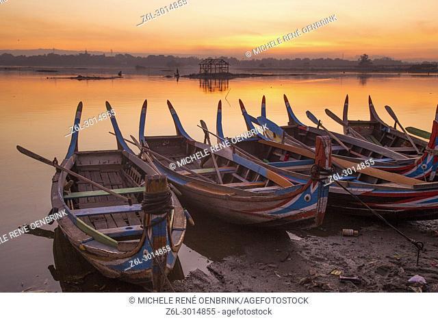 sunrise over the lake with fishermen on boats fishing in the lake near wooden foot bridge U Bein Bridge crossing the Taungthaman Lake near Amarapura in Mandalay...