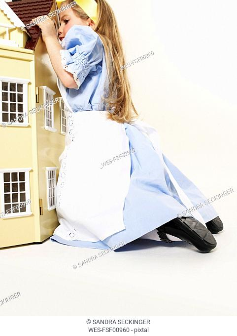 Little girl dressed up as Alice in Wonderland with doll's house