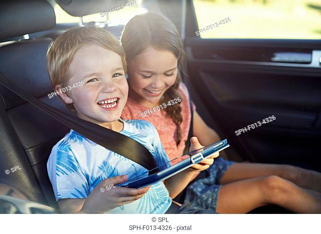 MODEL RELEASED. Brother and sister in the back seat of the car wearing seat belts, using a digital tablet