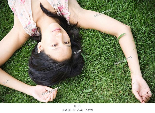 Portrait of woman laying in grass with arms over head