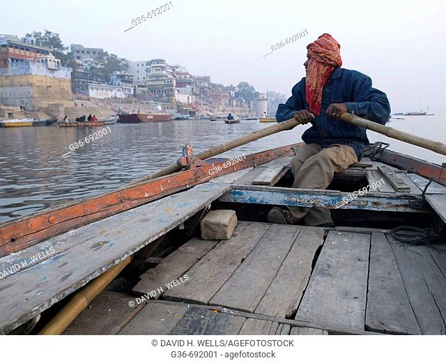 A boat man rows his boat to show visitors life along the holy river Ganges, an important pilgrimge site for Hindu's, in Varanasi, Uttar Pradesh, India