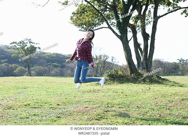 Young smiling woman jumping on grassland
