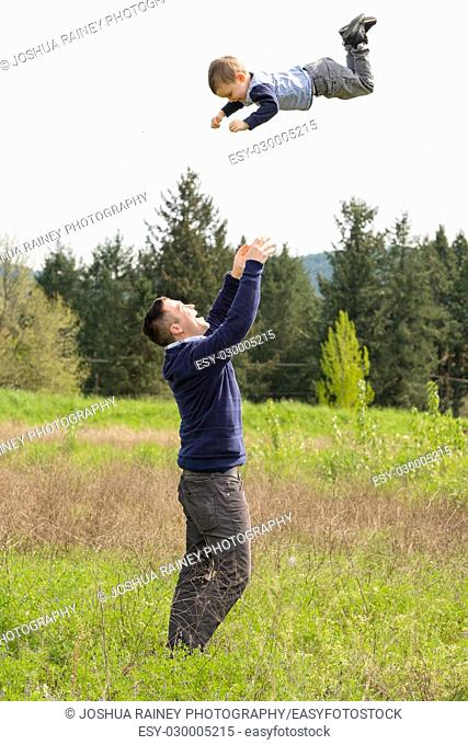 Father throwing his son very high in the air while standing outdoors in a natural field in Oregon