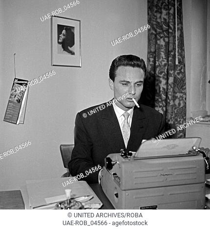 Der französische Sänger Johnny Grey am Schreibtisch an der Schreibmaschine, Deutschland 1950er Jahre. French singer Johnny Grey on his disk with a type writer