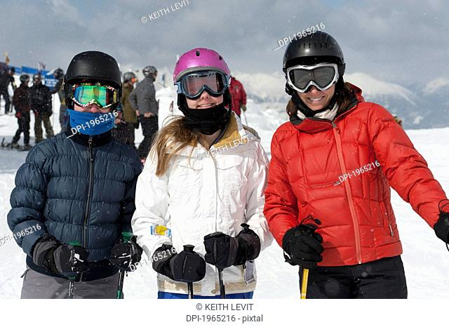skiers pose with mountains in the background, whistler british columbia canada