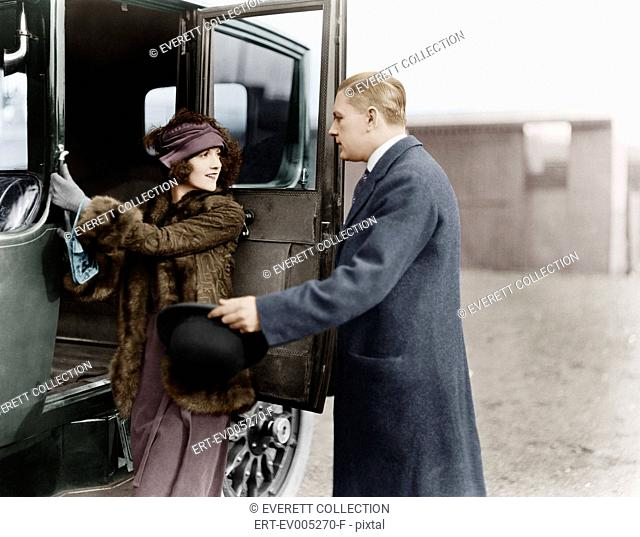Profile of a man helping a young woman board a car All persons depicted are not longer living and no estate exists. Supplier warranties that there will be no...