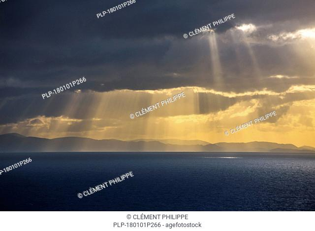 Sunrays bursting through dense sheet of rain clouds over sea water at sunset