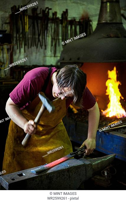 A blacksmith strikes a length of red hot metal on an anvil with a hammer in a workshop