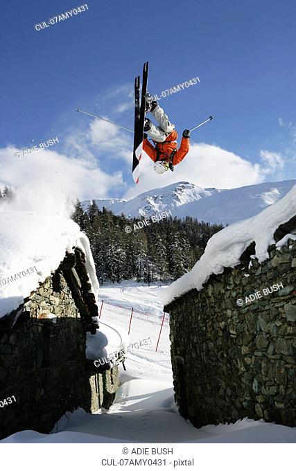 Skier jumping between buildings