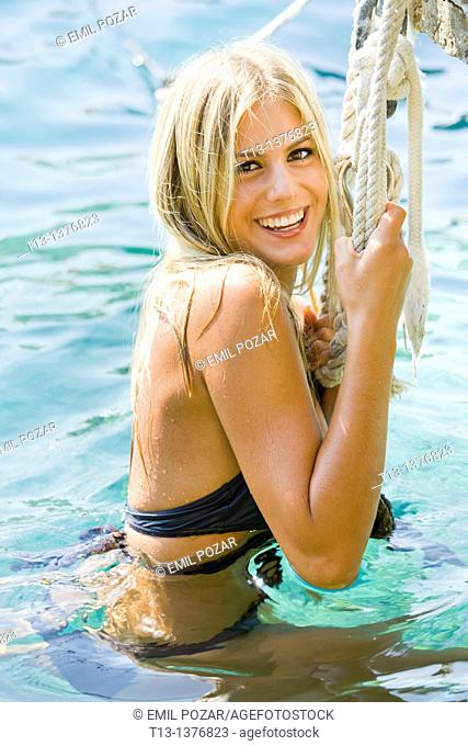 Happy young woman in water is holding a rope