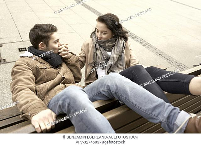 teenage man kissing hand of woman, young couple sitting upside down on bench, in Cottbus, Brandenburg, Germany