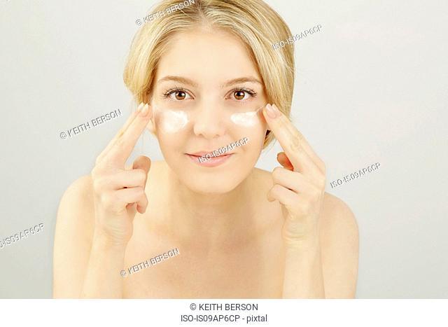 Portrait of blonde woman applying face cream