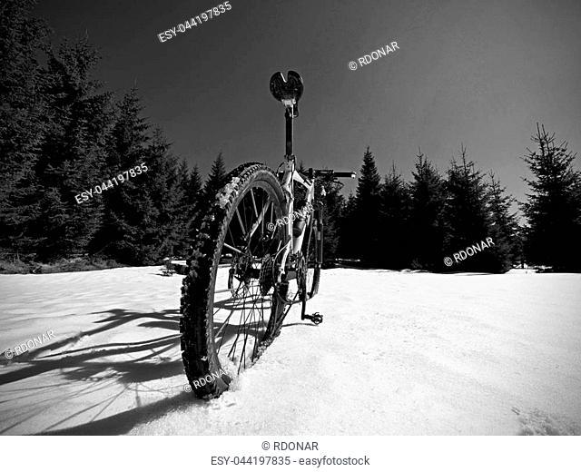 Mountain bike standing in frozen snow against blue sky. Hidden asphalt road under sow cover. Extreme adrenalin sports