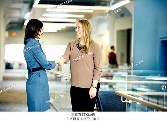 Caucasian businesswomen shaking hands in office