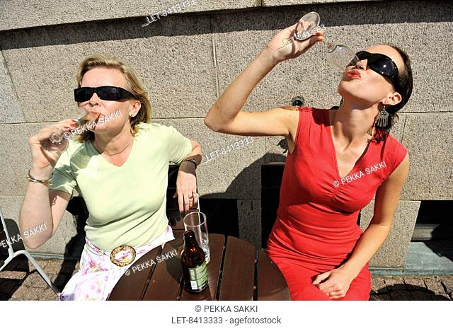 People sit at an outdoor restaurant in Helsinki. Two women drinking sparkling wine