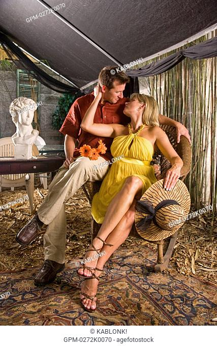 Romantic couple sitting together on wicker chair