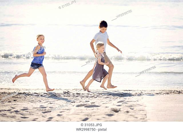 Boy and two girls running along a sandy beach by the ocean